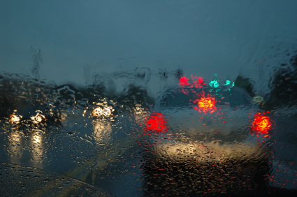 rainy view of the back of a police car with lights on